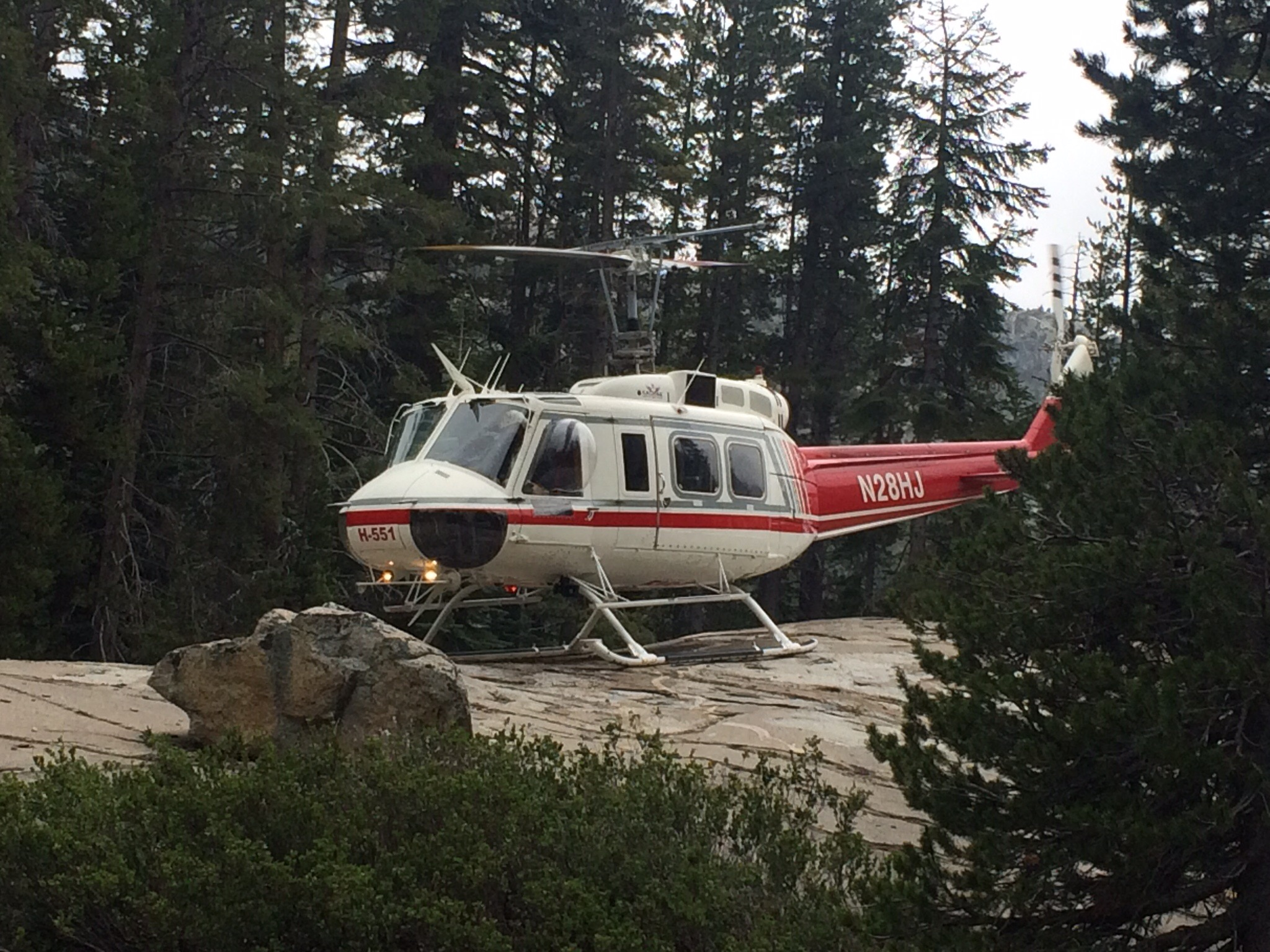 Rescue helicopter that somehow managed to land on a big rock in a small clearing.